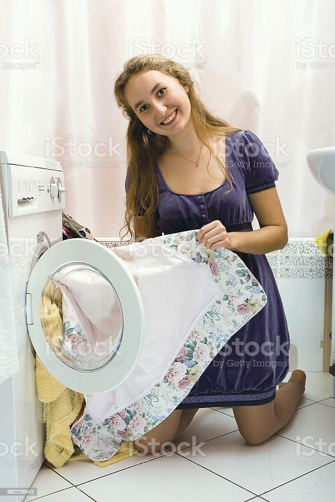 Ragazza prendendo clothers in lavatrice foto stock royalty-free