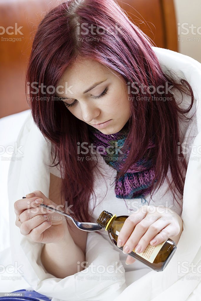 Girl taking cough syrup royalty-free stock photo