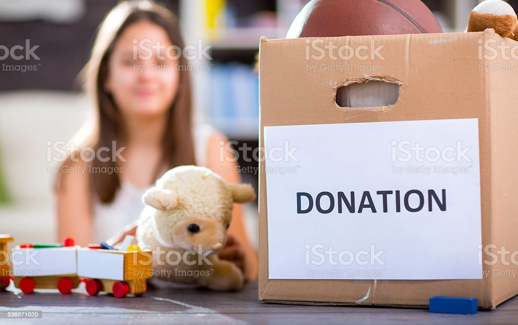 Girl taking donation box full with stuff for donate stock photo