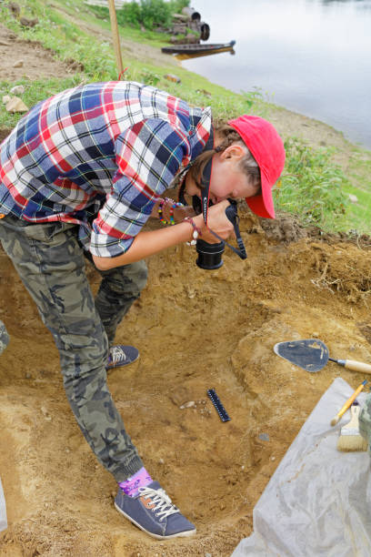 Girl taking photo of archaeological finds during a field expedition-ancient beads stock photo