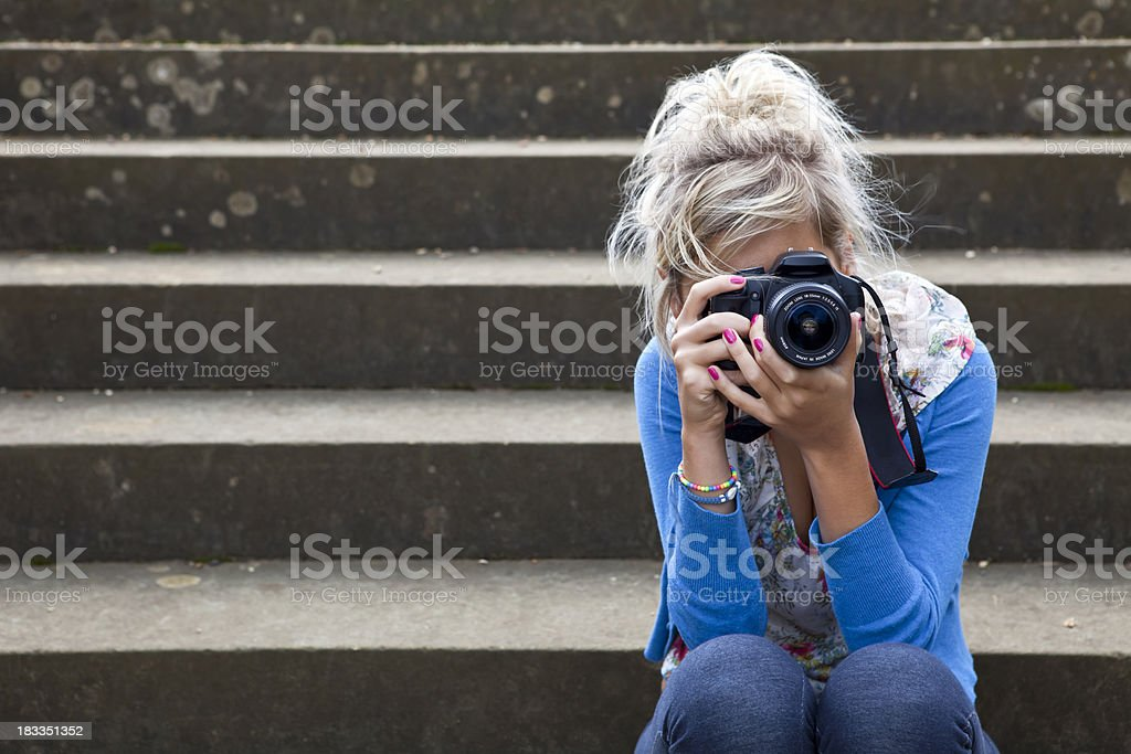 Girl Taking Photograph Sitting on Stone Steps royalty-free stock photo