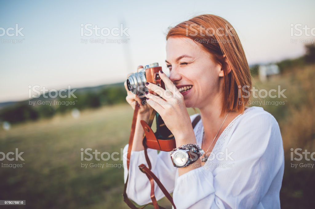 Girl taking picture with her retro camera and have fun. stock photo