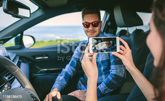 Girl taking a picture with the cell phone to her boyfriend in the car. Selective focus on mobile in foreground