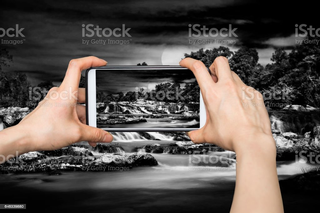 Girl taking pictures in The dark waterfall stock photo