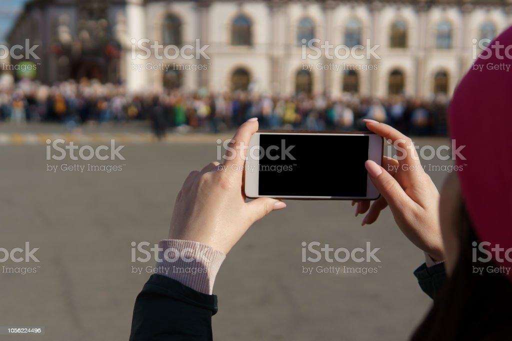 fille de prendre des photos de gens de la foule sur le téléphone - Photo