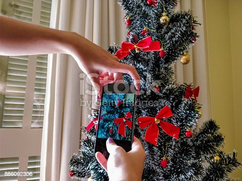 girl taking pictures of the Christmas tree with her new cell phone