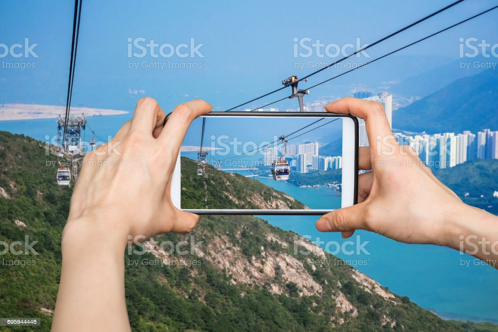 Girl taking pictures on mobile smart phone in Cable car,from Hong...