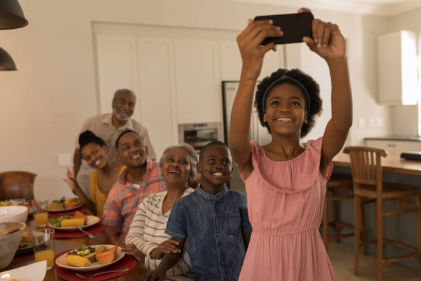 Girl taking selfie of family with mobile phone on dining table at home stock photo