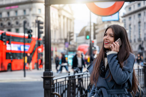 Girl talks on her mobile phone in Piccadilly Circus in London , UK A urban city girl stands on the underground station of Piccadilly Circus in London , UK, and talks on her mobile phone central london stock pictures, royalty-free photos & images