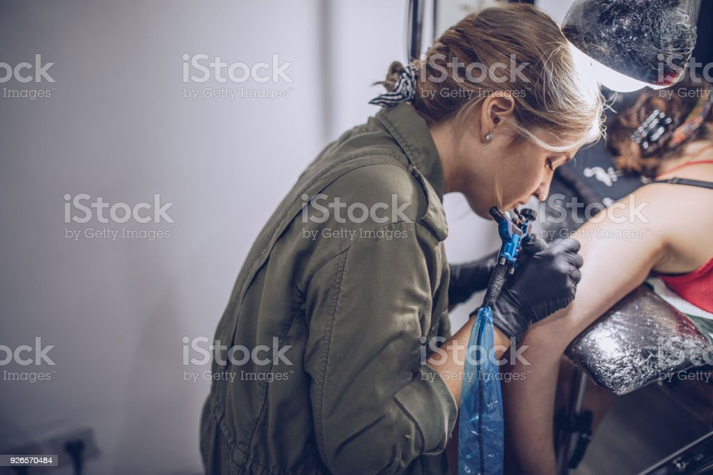 Girl tattoo artist working stock photo