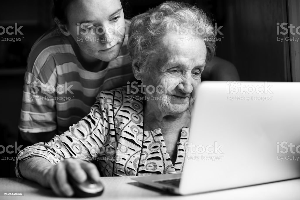 Girl teaches an elderly woman working on a laptop. Black-and-white photo. stock photo
