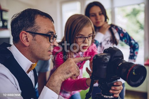 Little girl teaching how to use digital camera