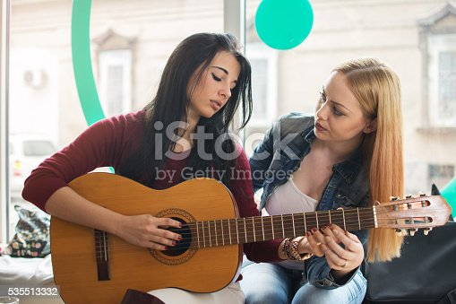 1155122702 istock photo Girl teaching her friend to play guitar. 535513332