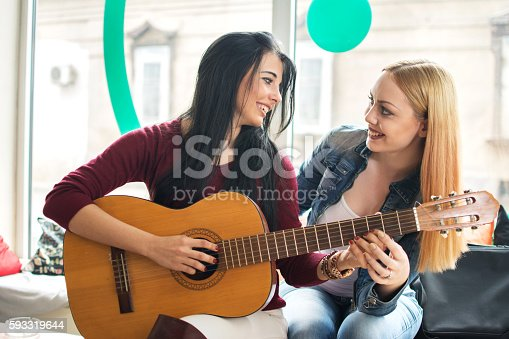 1155122702 istock photo Girl teaching her friend to play guitar. 593319644