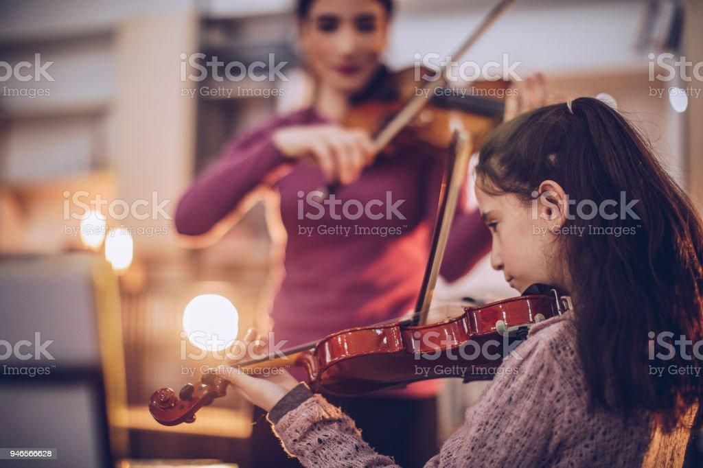 Girl teaching to play violin in music school