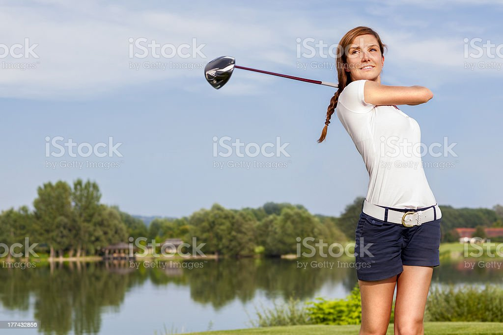 A girl teeing off playing golf on a course stock photo