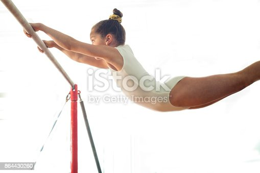 girl teenager doing sports in the gym on the crossbar