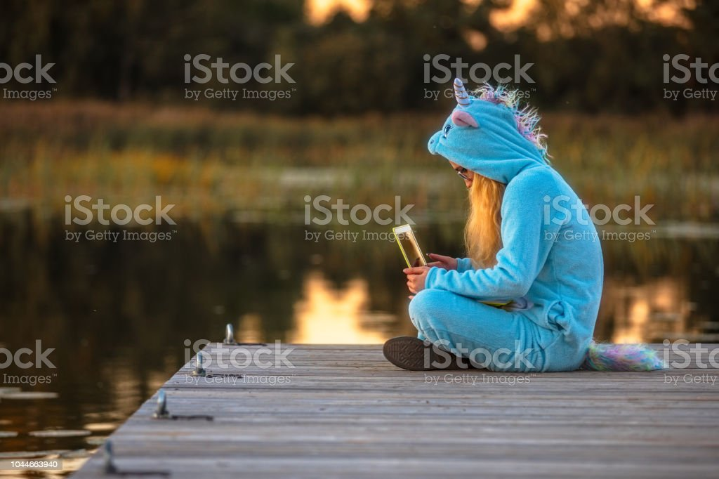 Girl teenager in a unicorn costume in the nature stock photo