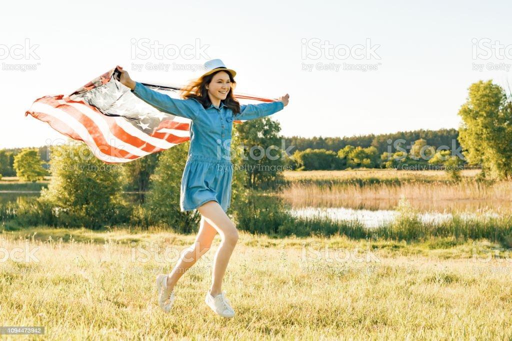 Kız Genç Amerikan bayrağı yaz yeşil çayırlarda günbatımında çalışan ile. Doğa arka plan, kırsal manzara stok fotoğrafı