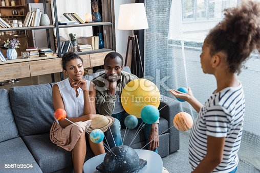 Little girl telling her parents about a big solar system model placed on the coffee table, while they are listening carefully