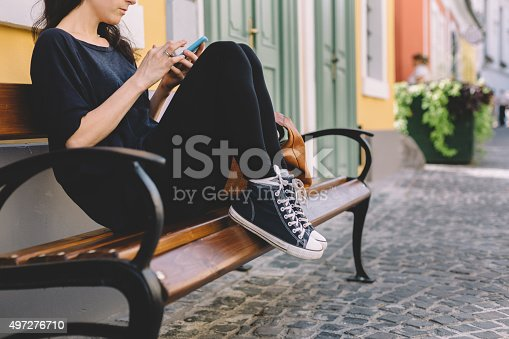 Woman sitting at bench and texting on smartphone
