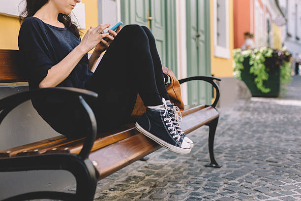 mädchen sms auf das telefon - sitzbank schuhe stock-fotos und bilder