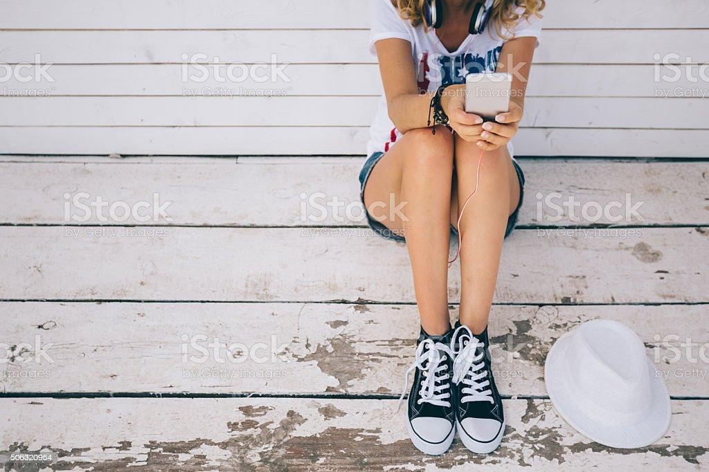Girl texting at the veranda stock photo