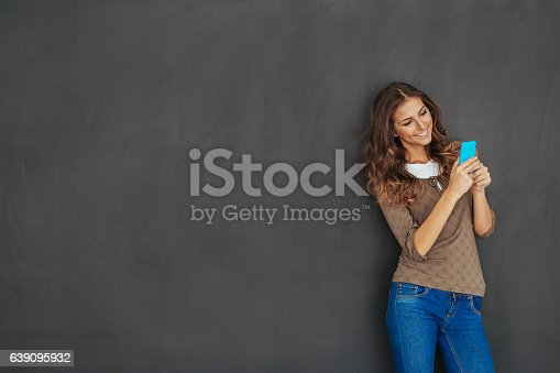 istock Girl texting in front of a blackboard 639095932