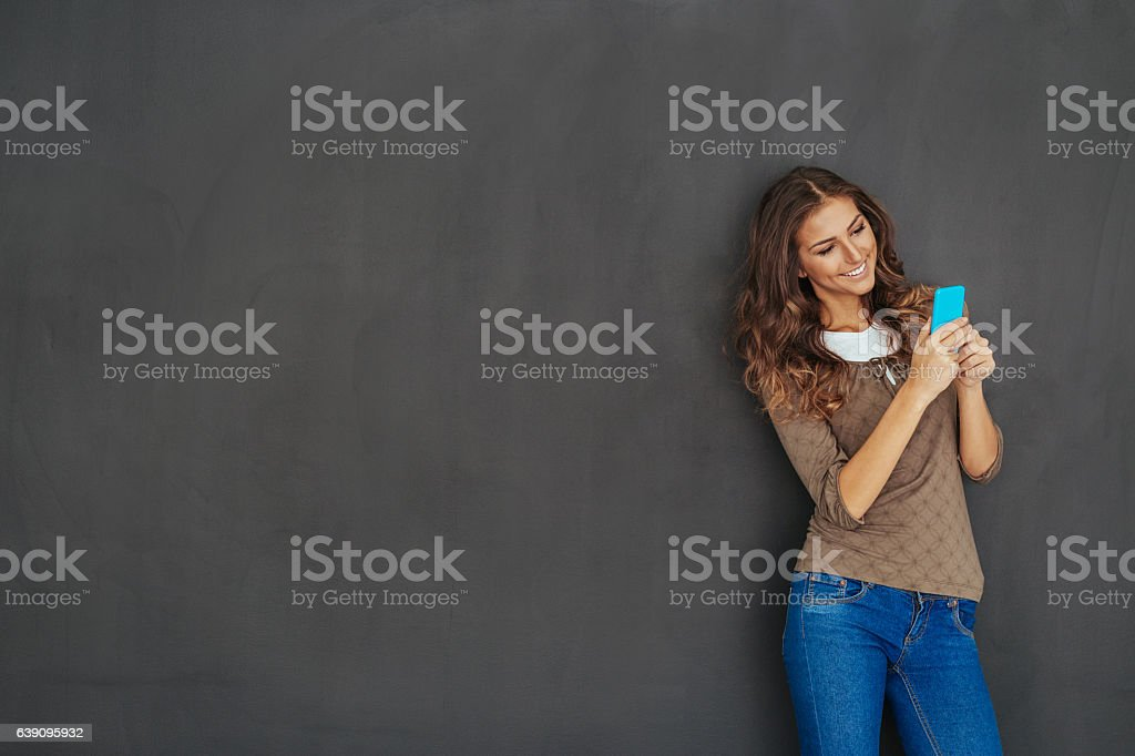Girl texting in front of a blackboard stock photo