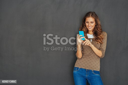 639569206 istock photo Girl texting in front of a blackboard 639310892