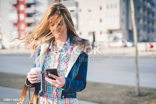Cute girl with a cup of coffee texting on a sidewalk in the city on a sunny day