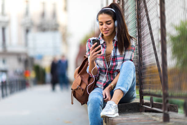 Girl texting on smartphone in the city stock photo