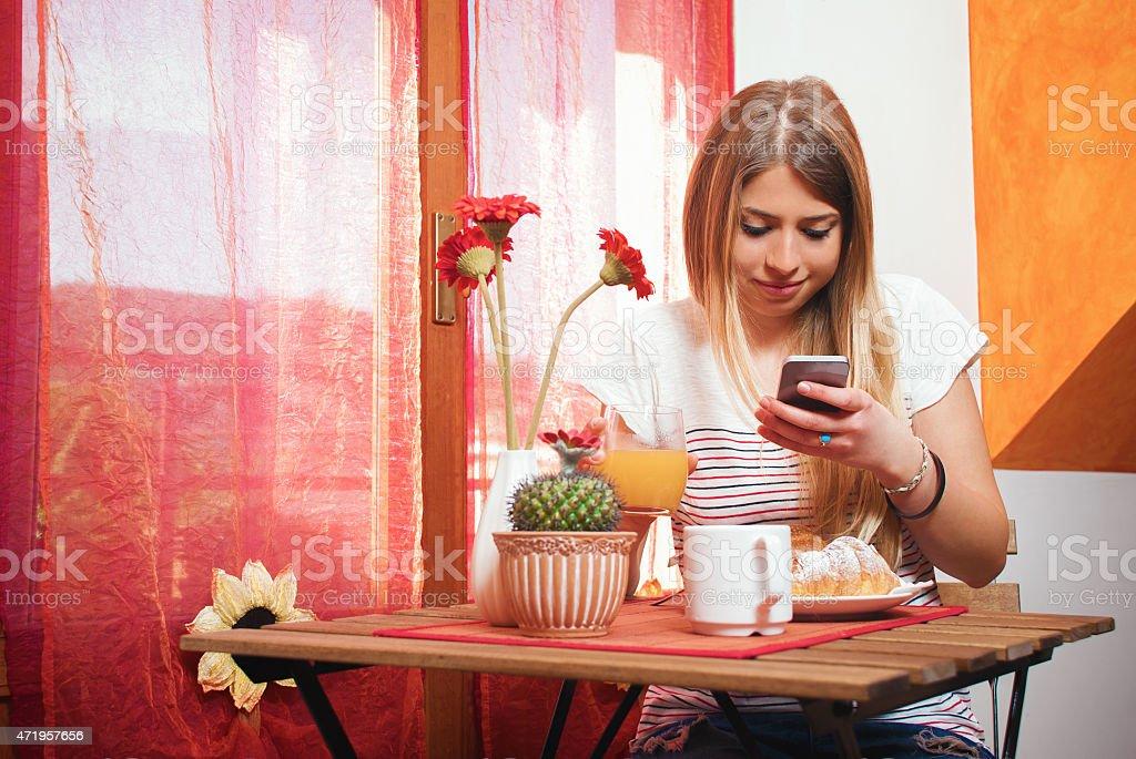 Mädchen SMS auf dem Handy während Frühstück – Foto