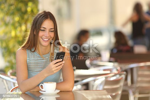 istock Girl texting on the phone in a restaurant 525937251