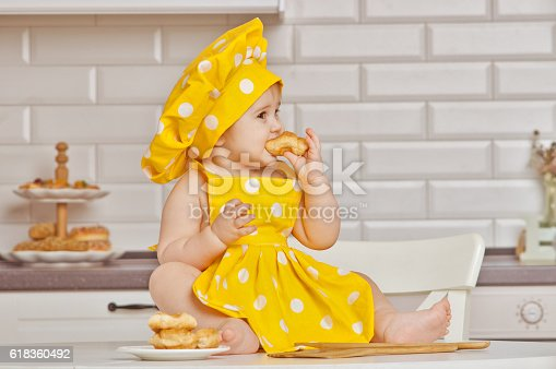 istock girl the child in a yellow suit of the cook 618360492