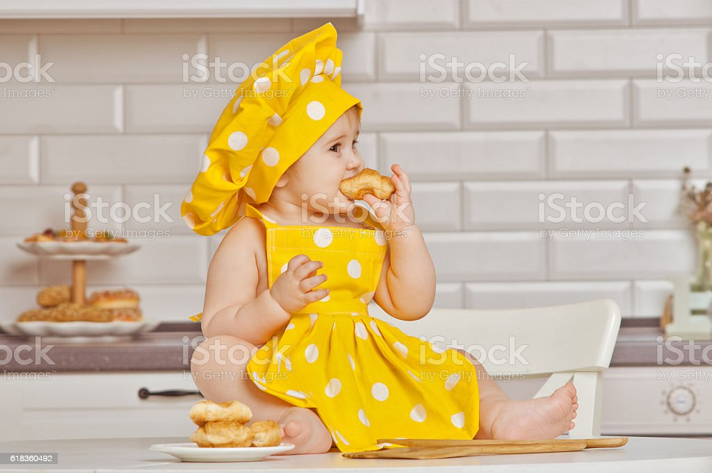 girl the child in a yellow suit of the cook stock photo