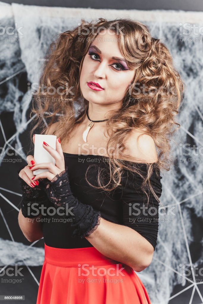 1100a1e609 Girl the witch in front of black wall in a blouse and red skirt for  Halloween with candle - Stock image .