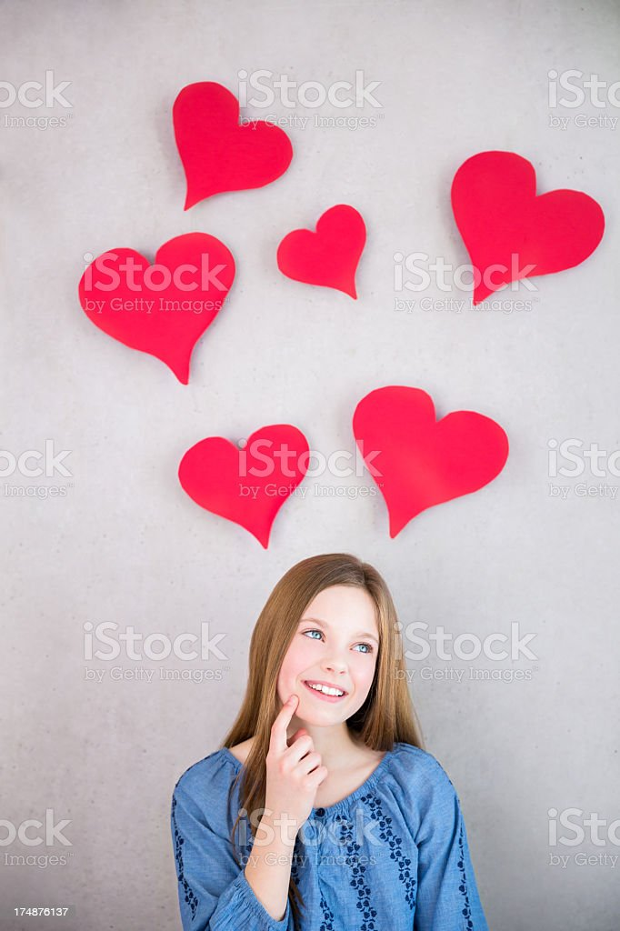 Girl thinking with hearts above her head royalty-free stock photo