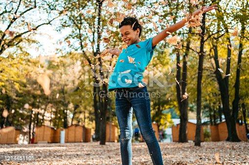 Joyful mix race girl throwing leaf in public park.