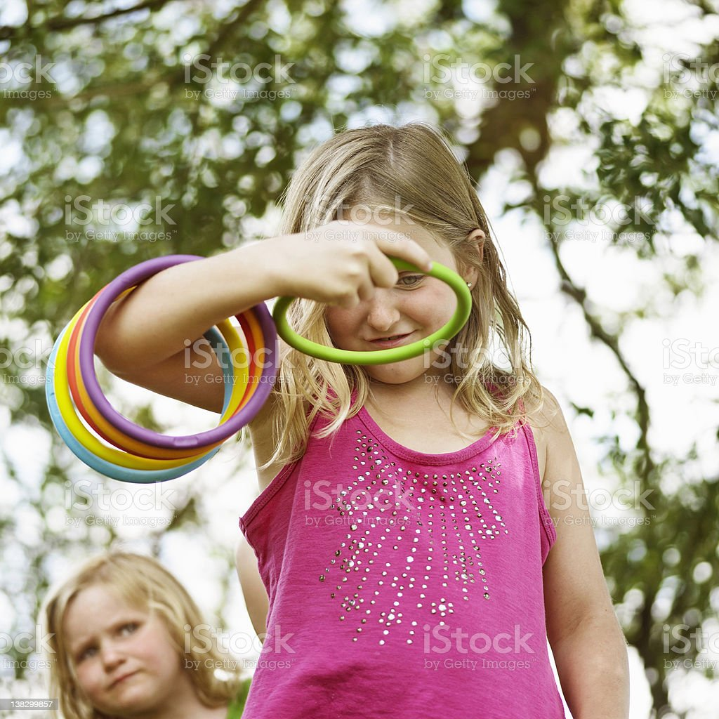 Girl throwing rings outdoors stock photo