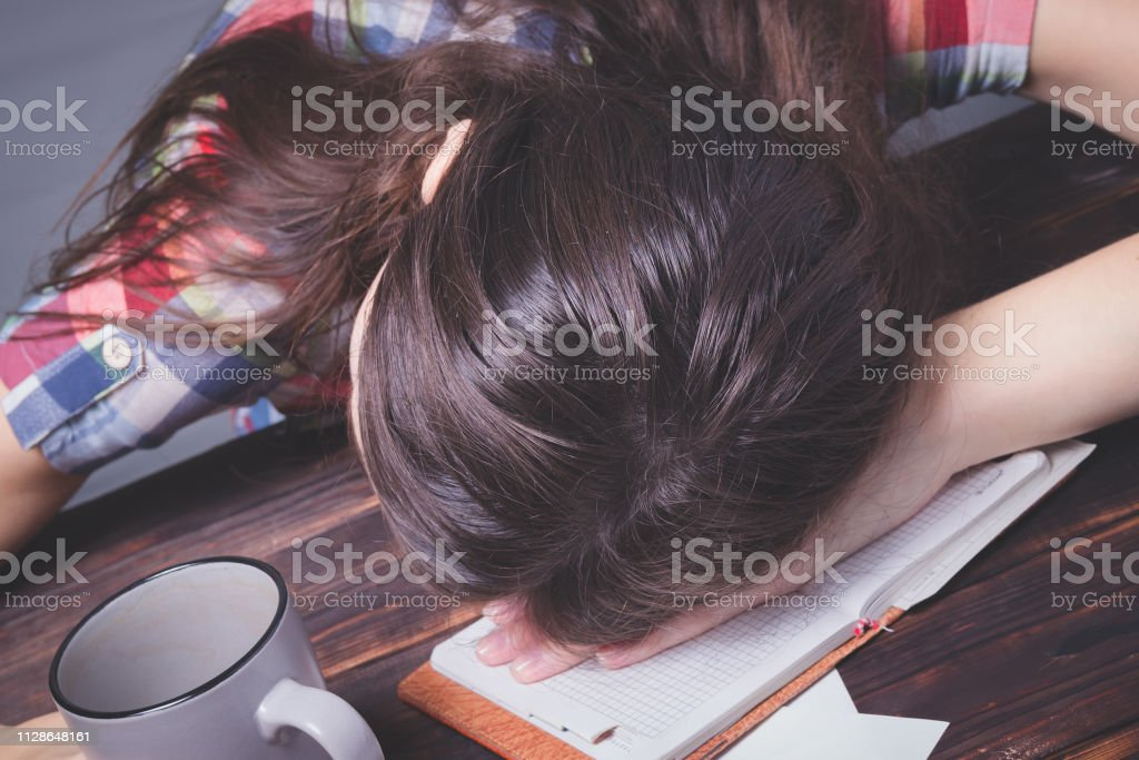 Girl tired student falls asleep. Study session. Education