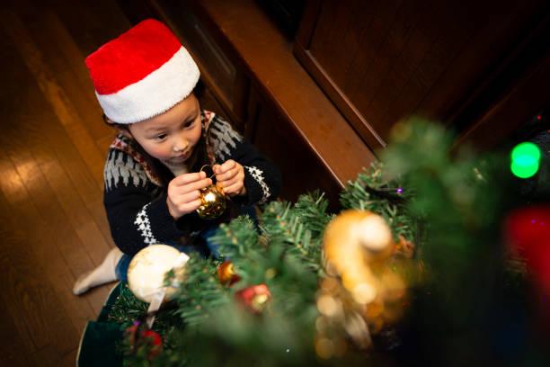 mädchen zu den weihnachtsbaum schmücken - weihnachten 7 jährige stock-fotos und bilder
