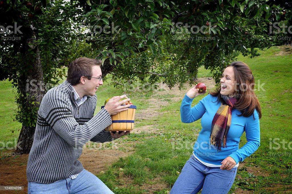 Girl Tossing Apple at Boyfriend's Basket stock photo