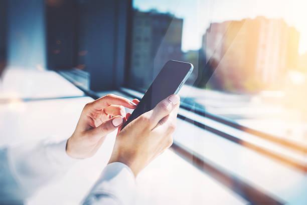 Fille de toucher l'écran de son Smarthone. Arrière-plan flou, horizontales - Photo