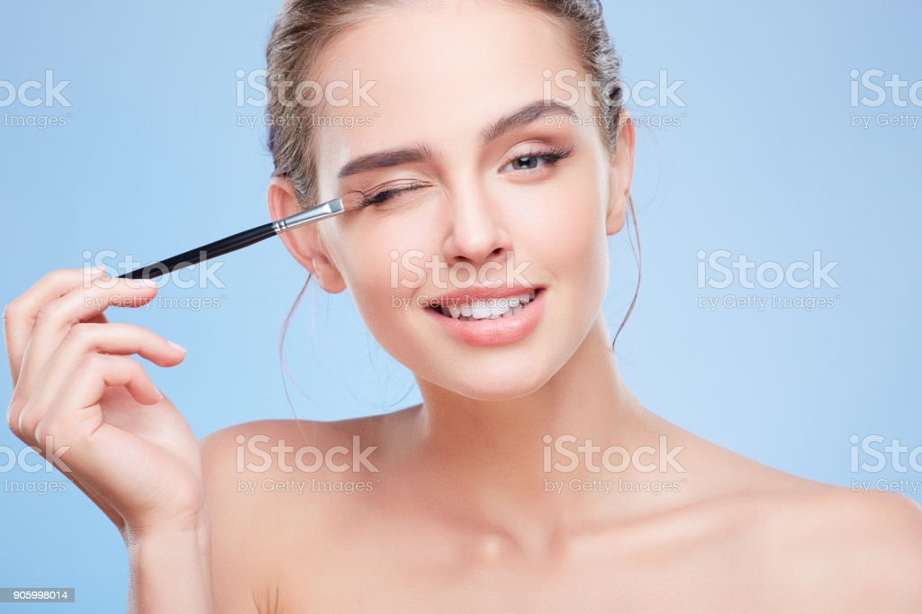 Girl touching eyelid with brush stock photo