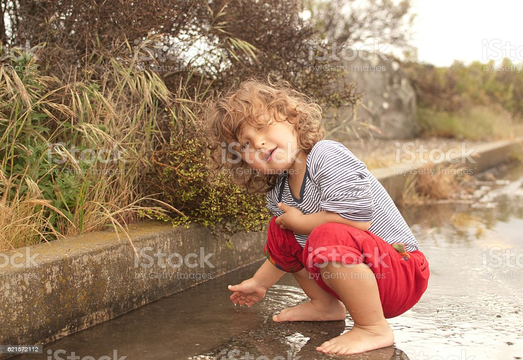 Girl touching rain puddle photo libre de droits