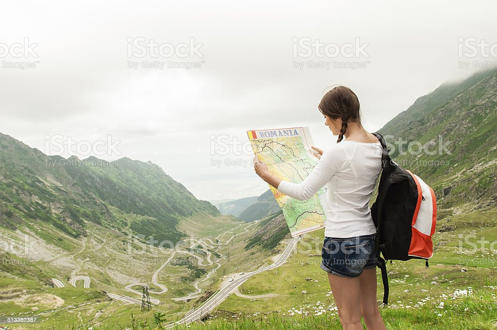 Girl tourist in mountain read the map stock photo