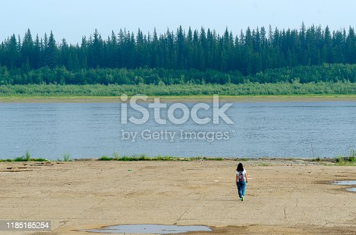 Girl tourist lonely goes to a concrete cliff on the shore of the old pier at the Northern river vilyu with spruce tundra forests of Yakutia on the other side.