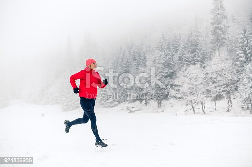 484750230 istock photo Girl trail running on snow in winter mountains 924836936