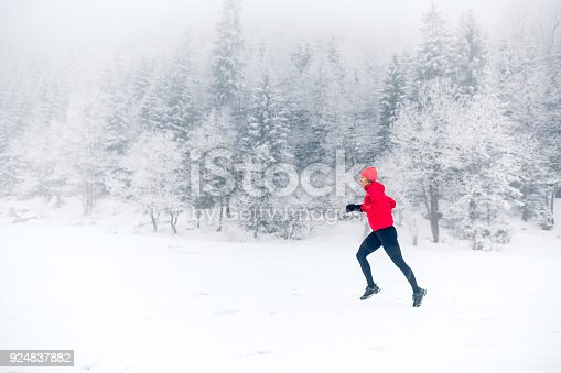 484750230 istock photo Girl trail running on snow in winter mountains 924837882